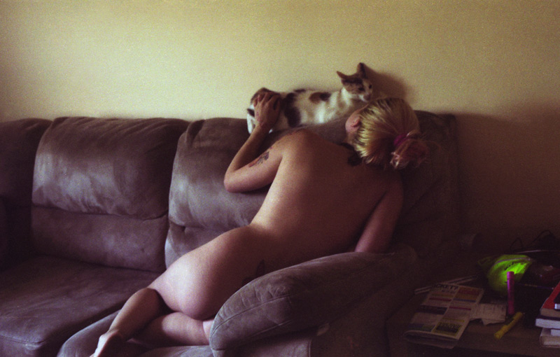 Nude girl on a sofa with a cat
