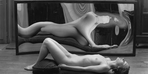 Black and white photo of a nude woman distorted in a mirror