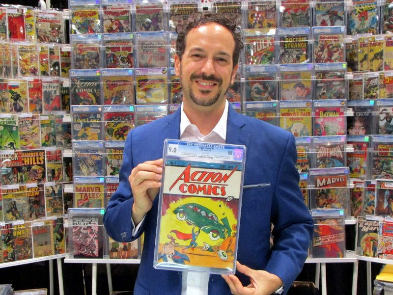 man holding up action comics #1