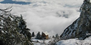 Small wooden house on a mountain above the clouds